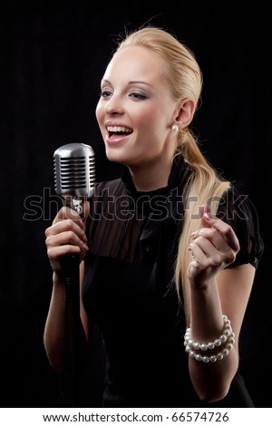 An elegant female singer with microphone - stock photo