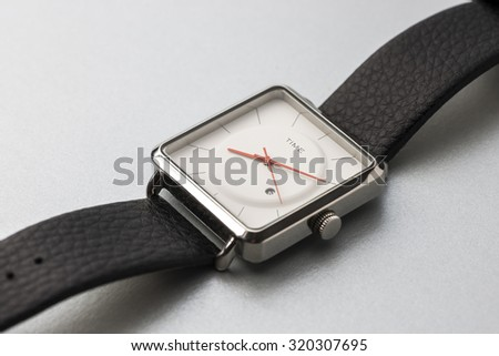An elegant gent's wrist watch with white dial. Close up of watch with open strap. - stock photo