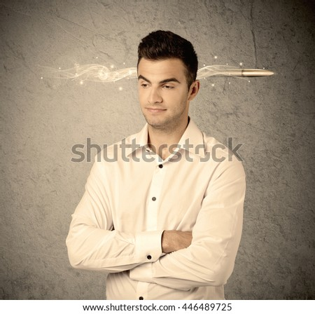 An elegant handsome business guy standing in front of wall with a bullet going through his head, making facial expressions concept