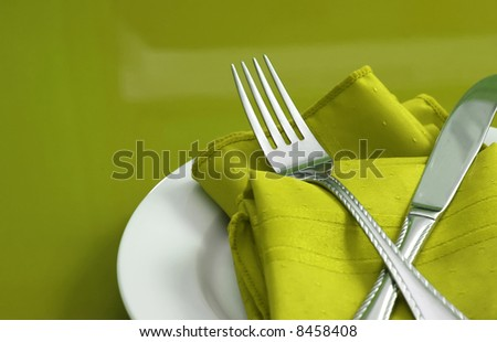 An elegant holiday table setting with fork, knife and napkin - stock photo
