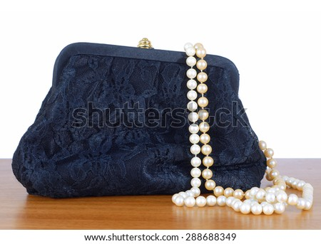 An elegant, lacy black clutch woman's evening bag laying on a wooden table, isolated on white. Two strings of pearls are spilling out of the bag.  Isolated on white. Concept of feminine glamour - stock photo