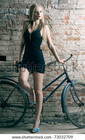 An elegant long-legged young woman with a bicycle against a brick wall. - stock photo