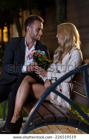 An elegant man giving his date a bunch of flowers on a bench - stock photo