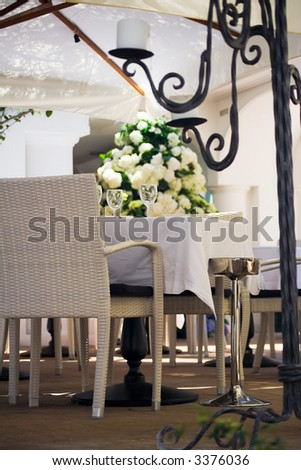 An elegant outdoors table setting with chairs at a luxury hotel in Capri surrounded by flowers, partially behind an iron candelabrum and below a parasol
