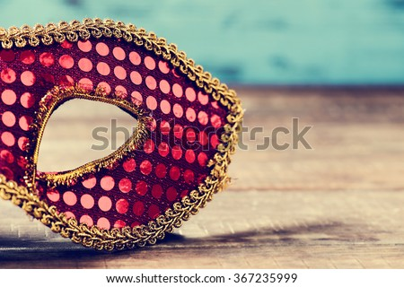 an elegant red and golden carnival mask on a rustic wooden surface - stock photo