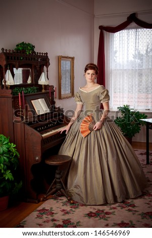 An elegant woman dressed in a Civil War era ball gown stands by a vintage organ with fan - stock photo