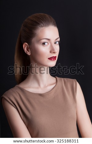 An elegant woman in a cream dress with evening make-up on her face on a black background.Girl with cherry lips and beautiful smooth skin on the face.Portrait of a woman with brown hair.Makeup
