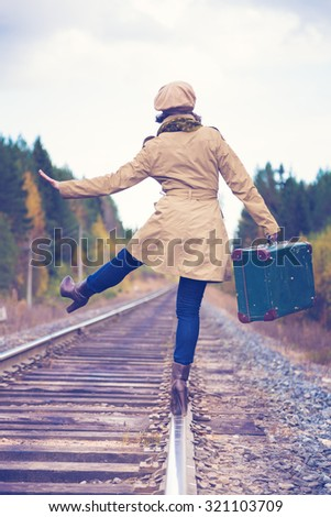 An elegant woman with a suitcase traveling by rail autumn day.