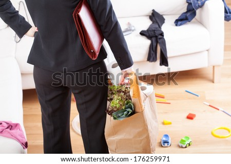 An elegant woman with grocery shopping left in a messy home - stock photo