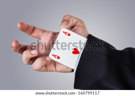 an elegant young businessman making card tricks with poker cards