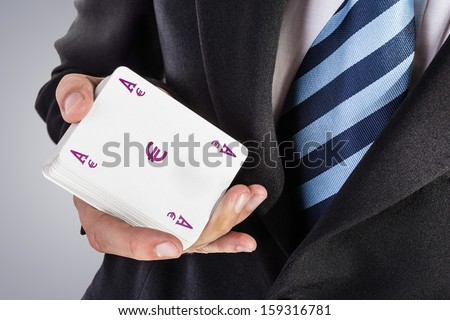 an elegant young businessman showing an ace in his hand