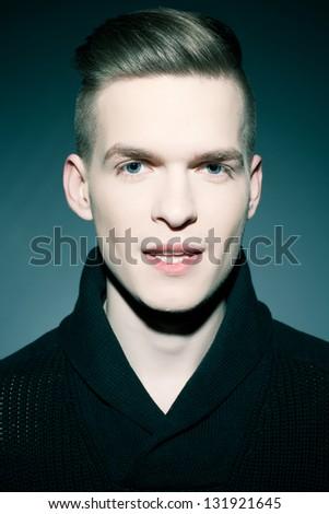 An elegant young handsome man posing over dark blue background. Studio fashion portrait. - stock photo