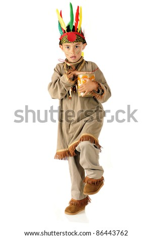 An elementary-aged boy high-stepping an Indian War Dance while in costume and beating his drum.  On a white background. - stock photo