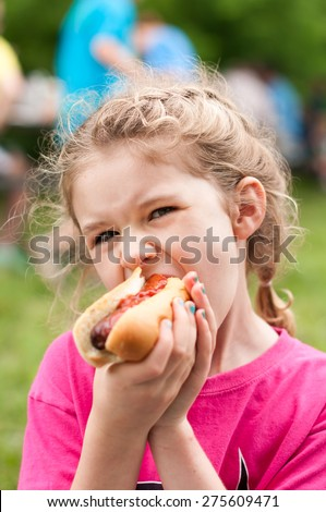An elementary aged little girl is outdoors eating a hot dog.  She holds the hot dog in both hands as she takes a huge bite.  She is wearing a bright pink shirt and blue nail polish. - stock photo