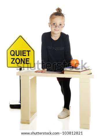 """An elementary-aged """"teacher"""" standing behind her desk by a """"Quiet Zone"""" sign.  On a white background. - stock photo"""