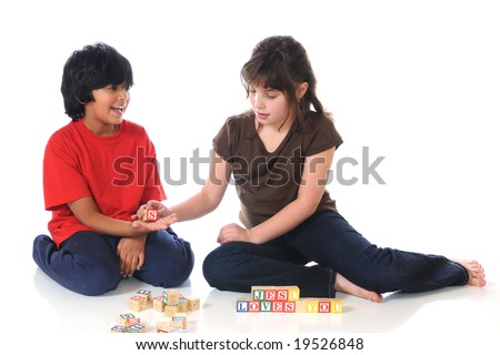 """An elementary boy and girl together spelling out """"Jesus Loves You"""" in alphabet blocks. - stock photo"""