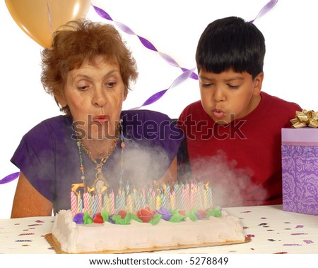 An elementary boy and his eighty year-old great grandmother blow out her birthday candles.  Fire and smoke!  Isolated on white. - stock photo