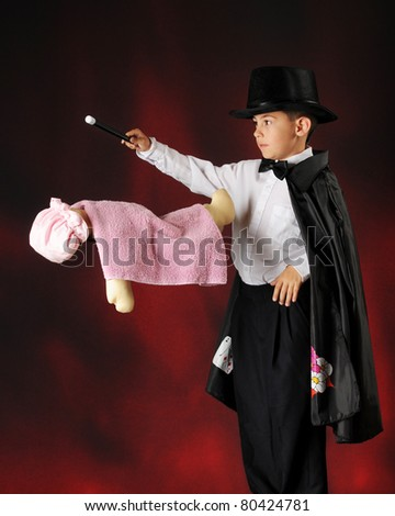 An elementary boy concentrating as he levitates a doll with his wand. - stock photo