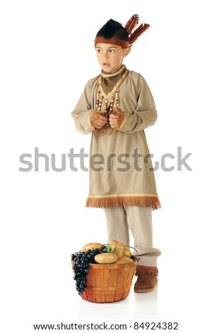 An elementary boy dressed as a native American Indian.  A basket of grapes and potatoes is at his feet -- his contribution for the first Thanksgiving feast. - stock photo