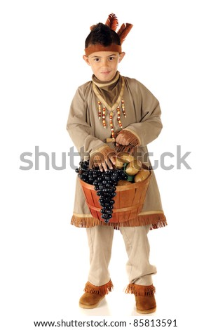 An elementary boy dressed as a native American Indian, carrying a basket filled with grapes and potatoes.  Isolated on white. - stock photo