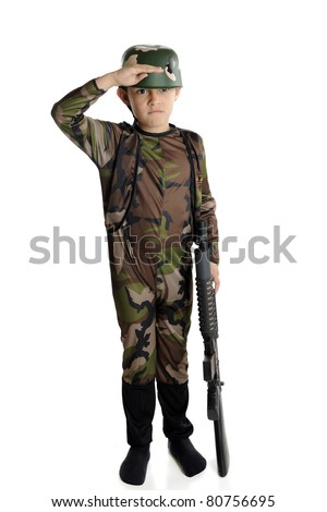 An elementary boy fully dressed in military camouflage and helmet, saluting with his right hand while balancing a toy machine gun with his left. - stock photo