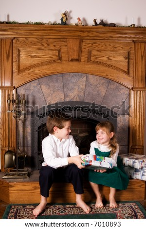 An elementary boy handing a Christmas gift to his little sister, both sitting on the family hearth.