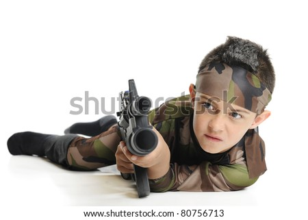 An elementary boy in army camouflage, aiming his toy machine gun as he crawls on his belly.  Isolated on white. - stock photo