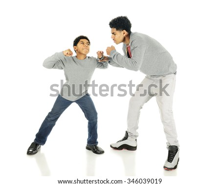 An elementary boy raising his fists towards his much taller older brothers.  On a white background. - stock photo