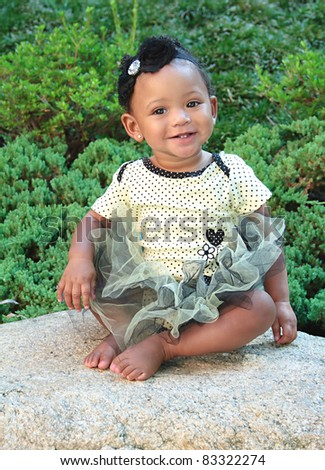 An Eleven Month Old Girl on a Rock with a tutu on.  She is smiling and very happy. - stock photo