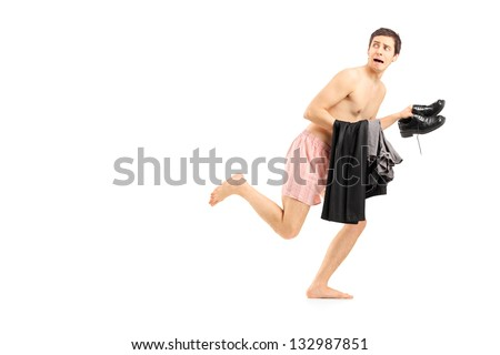 An embarrassed naked man in underwear holding his clothes and running, isolated on white background - stock photo