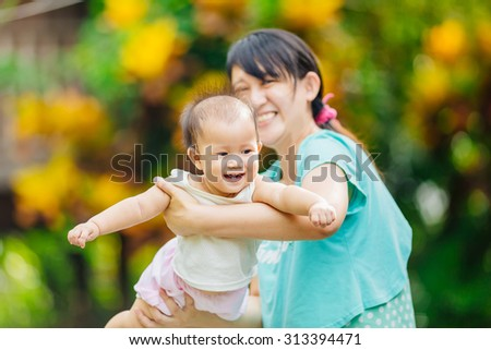 An emotional portrait of happy people. 9 months baby feeling happy and smiles with her mother in the garden.