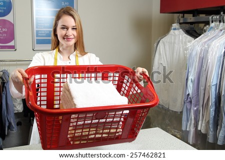 An Employee of a dry cleaning with a  laundry basket - stock photo