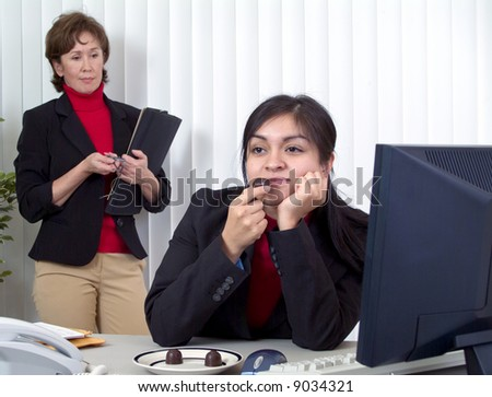 An employee off task, dreamily enjoying chocolate while an annoyed supervisor looks on. - stock photo