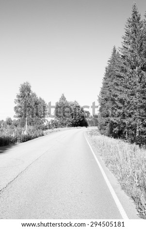 An empty asphalt road in Finland. Image taken during summer and image has a vintage effect applied.