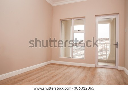 An Empty bedroom of a newly build house with laminated floor and glass windows and door that lead out to the patio. - stock photo