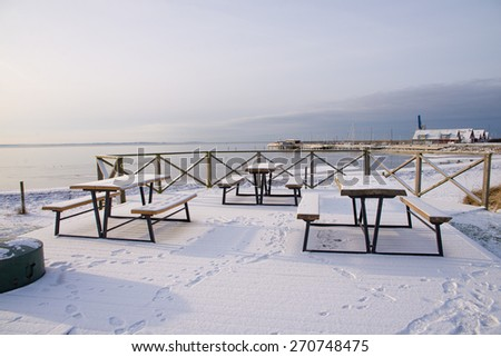 An empty bench on the beach - stock photo