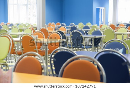 An empty cafeteria interior with blue, green, orange chairs - stock photo
