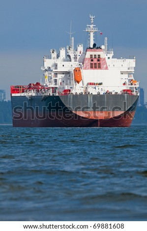 An empty cargo ship anchored just outside a port. - stock photo