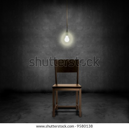 An empty chair and hanging light bulb in a dark room - stock photo
