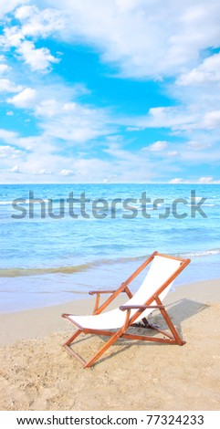An empty chair on a sandy beach near the water - stock photo