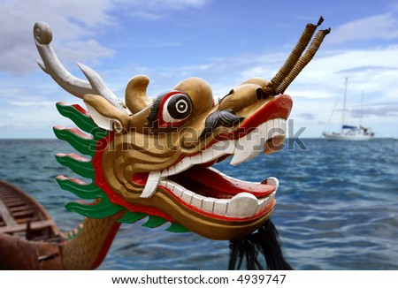 An empty Chinese Dragon boat waiting in the water. Focus is on the eye, the horizon is soft. - stock photo