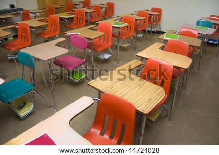 An empty class room with no students sitting in the desks. There are some notebooks laying around the room (none contain any logos.) - stock photo