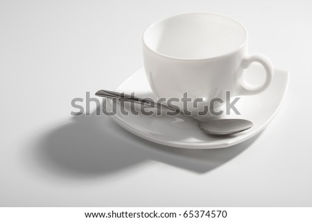 An empty coffee cup and teaspoon on a gray background with shadow