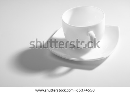 An empty coffee cup on a gray background with shadow - stock photo