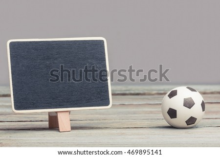 an empty, copy space chalkboard/blackboard/sign standing next to a miniature/toy soccer-ball. sports and exercise, concept image. wood panels and grey background.