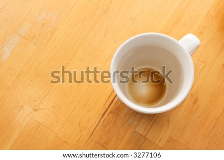 An empty cup of coffee viewed from above on a wooden table. - stock photo