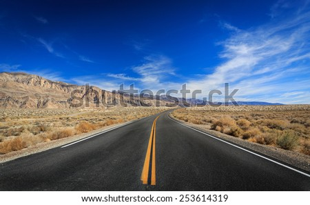 An empty desert road on the way to Death Valley National Park - stock photo