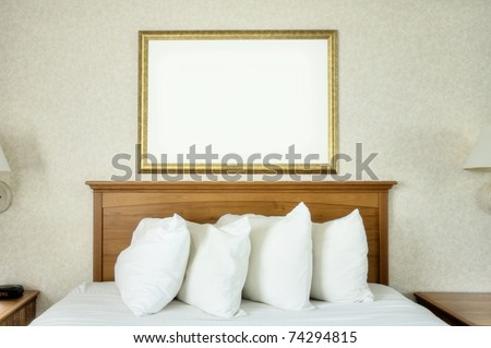 An empty frame hangs on the wall over a bed. - stock photo