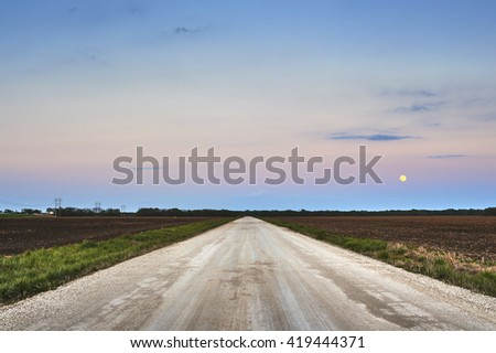 an empty gravel road with the moon in the sky - stock photo