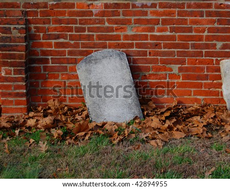 An empty gravestone: alone and forgotten against a brick wall.